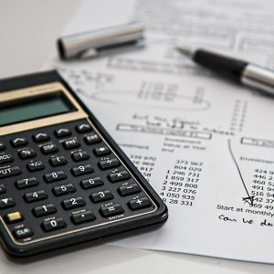 A calculator on pen resting on a balance sheet.