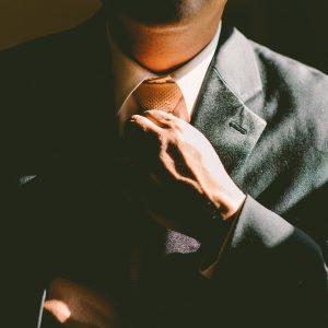 Man in gray suit straightening his necktie