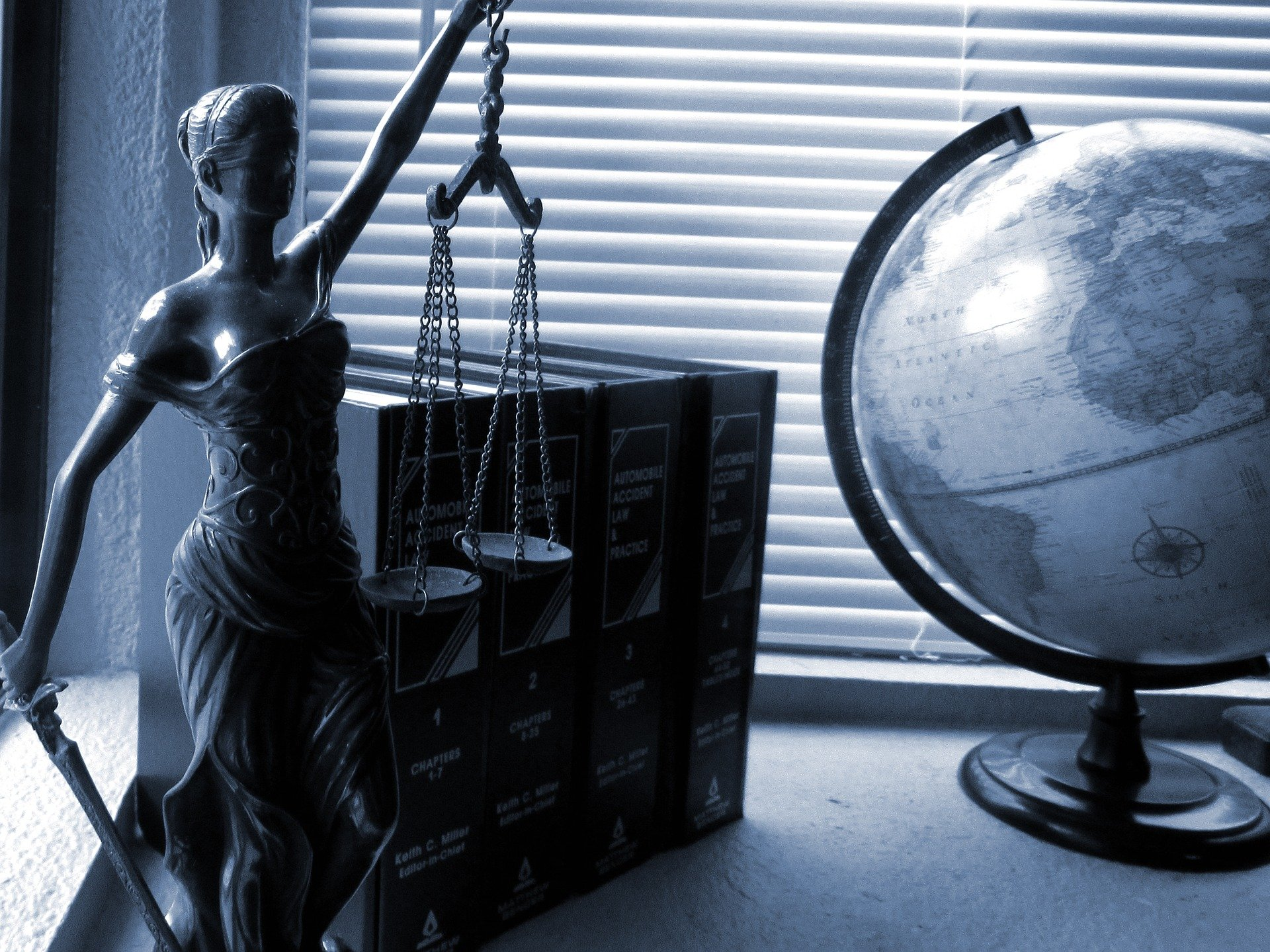 Lady justice, books, and a globe on a desk